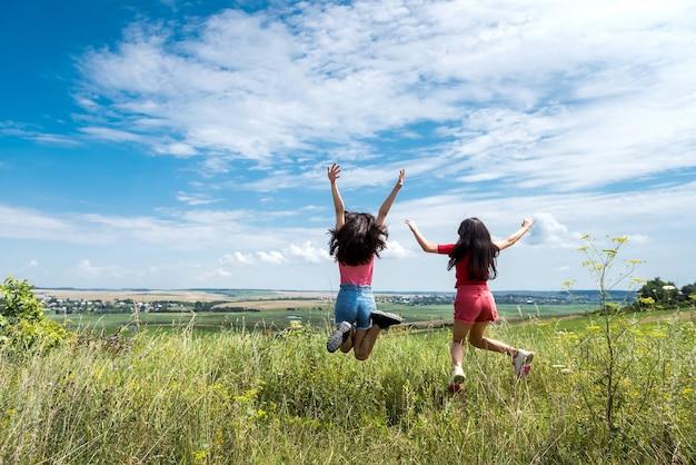 青い空の田園地帯で一緒にジャンプする2人の幸せなスリムな笑顔の若い女性