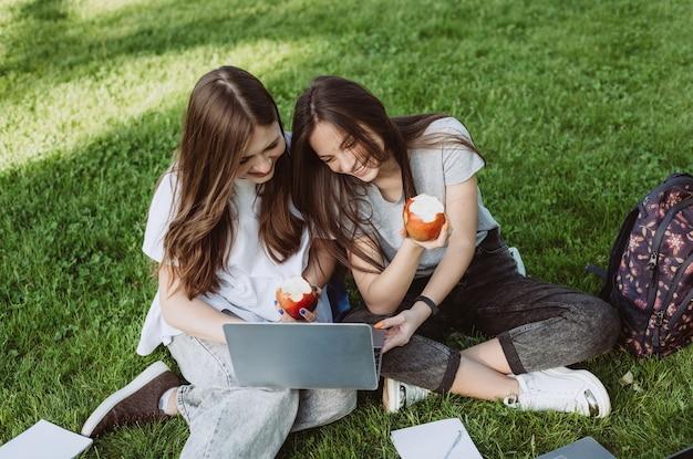 두 명의 행복한 미소를 짓고 있는 여학생들이 공원에 책과 노트북을 들고 공원에 앉아 사과를 먹고 공부하고 시험을 준비하고 있습니다. 원격 교육. 부드러운 선택적 초점입니다.