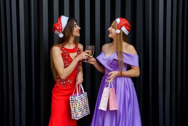 샴페인 잔으로 토스트 하는 크리스마스 모자에 두 행복 웃는 여자. 새해와 크리스마스 축하