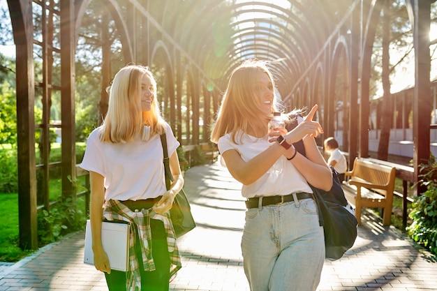 一緒に歩いている2人の幸せな笑顔の女の子10代の学生、バックパックを持つ若い女性、公園の背景で晴れた日