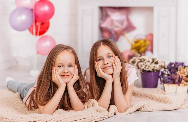 2人の幸せな笑顔の10代の少女が休日の部屋で遊ぶ