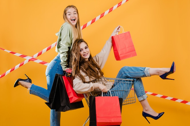 Two happy smiling women have cart with colorful shopping bags and signal tape isolated over yellow