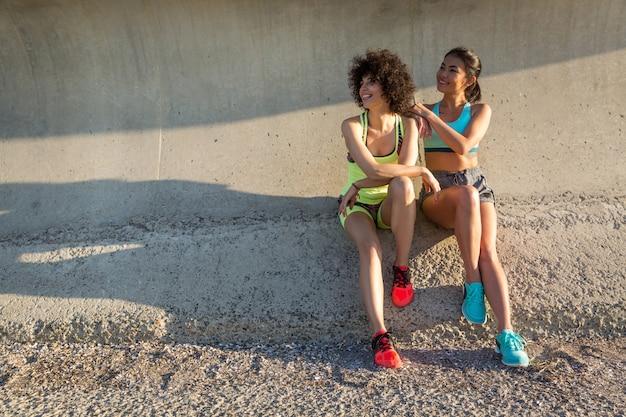 一緒に座っているスポーツウェアで2つの幸せなスポーティな女性