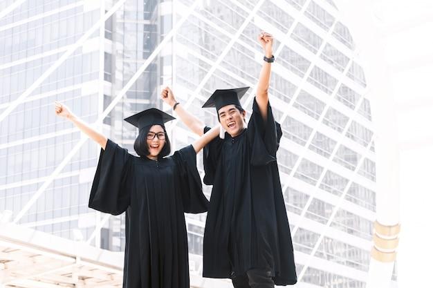 캠퍼스 건물 배경에 성공적인 졸업을 축하 두 행복 학생