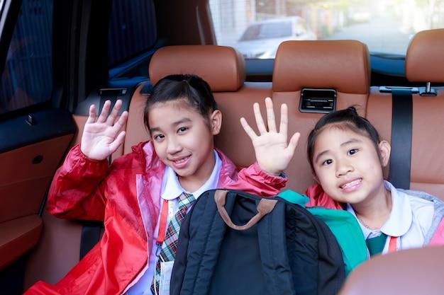 자동차 도로 여행을 즐기면서 손과 움직임을 올리는 두 행복 학생.