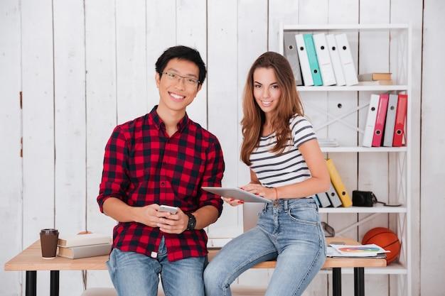 Два счастливых студента сидят на столе, держа в руках мобильный телефон и планшет