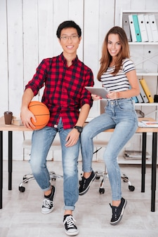 Two happy students sitting on table while holding basketball and tablet