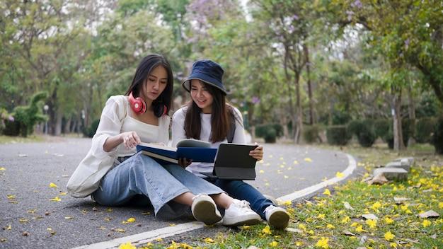 Два счастливых студента работают с цифровым планшетом и читают книгу, готовясь к экзаменам в университетском городке