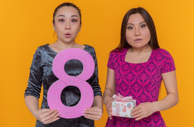 Two happy and surprised asian women celebrating international women's day holding number eight