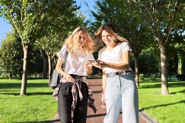 スマートフォンの画面を見ている2人の幸せな話を歩いている10代の少女、楽しんで笑って公園を歩いている大学生。 10代の若者、ライフスタイル、学生のコンセプト