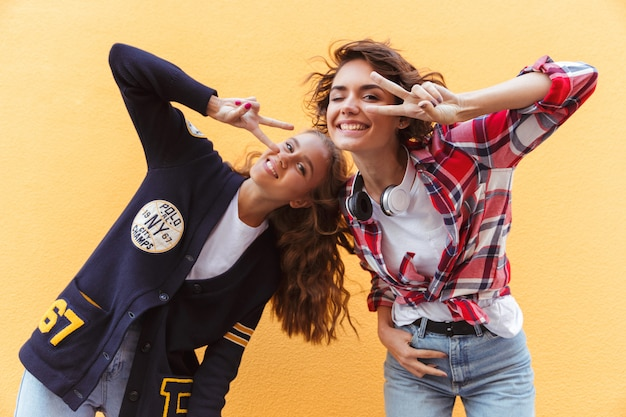 Two happy teenage girls showing peace gesture while having fun