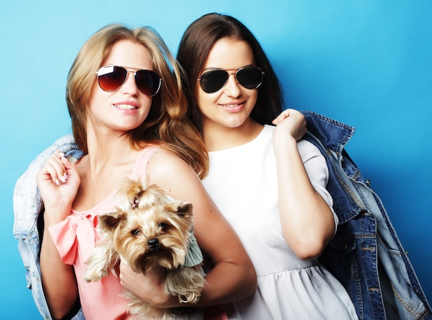 Две счастливые сестры-подростки с йоркширским терьером