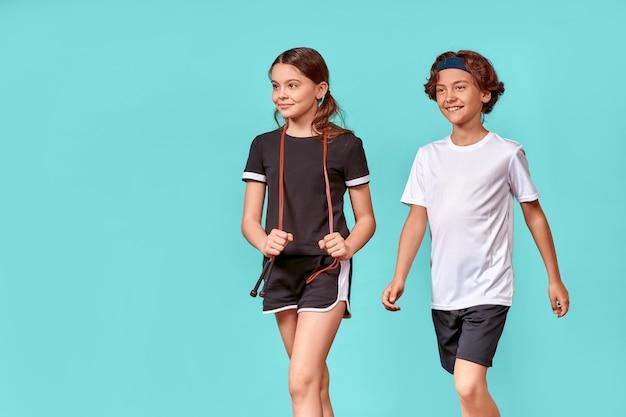 두 명의 행복한 10대 소년과 소녀, 줄넘기를 들고 멀리 바라보고 고립된 채 웃고 있다