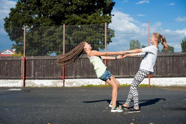 화창한 여름날 야외에서 즐거운 시간을 보내는 행복한 십대 소녀 두 명