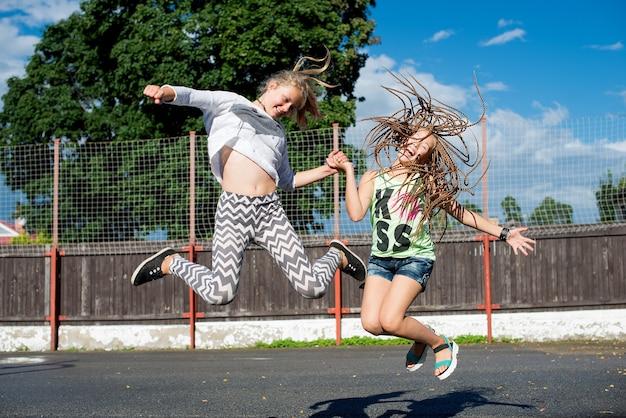 화창한 여름 날에 야외에서 즐거운 시간을 보내는 행복한 십대 소녀 2명