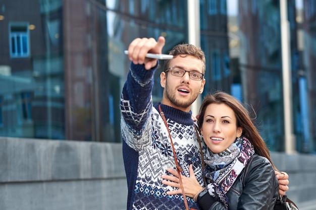 幸せな 2 人の観光客のカップルが、電話と地図を使って場所を探し、指で指を指しています。