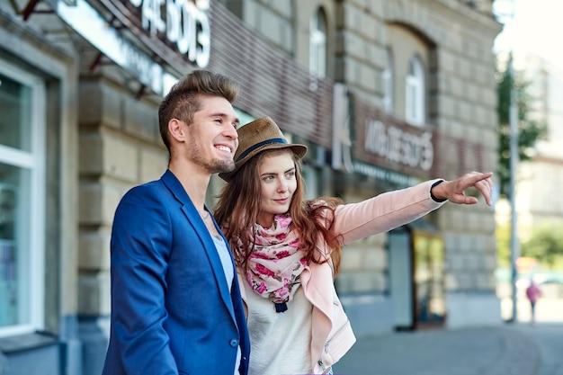 2人の幸せな観光客が、電話と地図を使って場所を検索し、指で指さします。