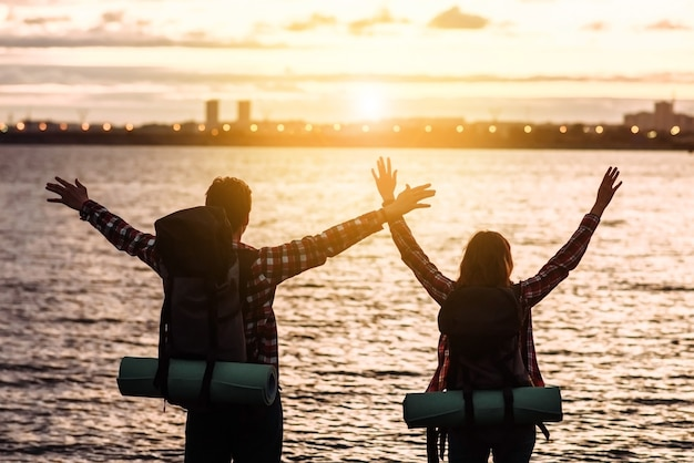 Two happy tourists, a man and a woman with backpacks, stand with raised hands and look at the mountain lake and the sunset. travel and vacation concept
