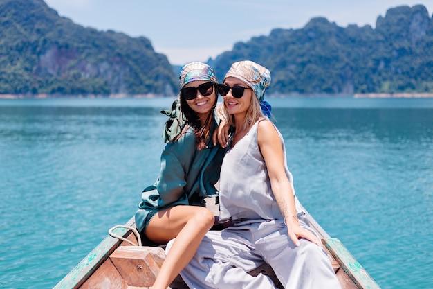 Два счастливых туристических друга-блогера женщины в шелковом костюме, шарфе и солнечных очках во время отпуска путешествуют по таиланду на азиатской лодке в национальном парке кхао сок. Бесплатные Фотографии