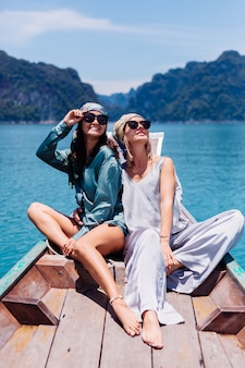 Два счастливых туристических друга-блогера женщины в шелковом костюме, шарфе и солнечных очках во время отпуска путешествуют по таиланду на азиатской лодке в национальном парке кхао сок.