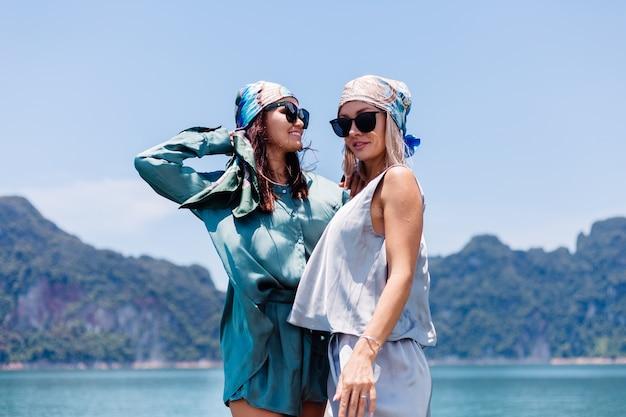 休暇中のシルクのスーツとスカーフとサングラスを身に着けた2人の幸せな女性ブロガーの観光客の友人が、アジアのボート、カオソック国立公園でタイを旅します。
