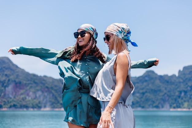 실크 양복과 스카프와 선글라스에 두 행복 한 여자 블로거 관광 친구 휴가 아시아 보트, 카오 속 국립 공원에서 태국 여행.
