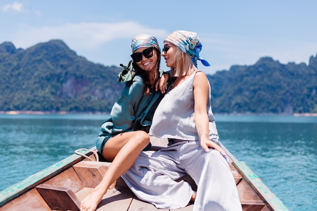 Two happy woman blogger tourist friends in silk suit and scarf and sunglasses on vacation travel around thailand on asian boat, khao sok national park.