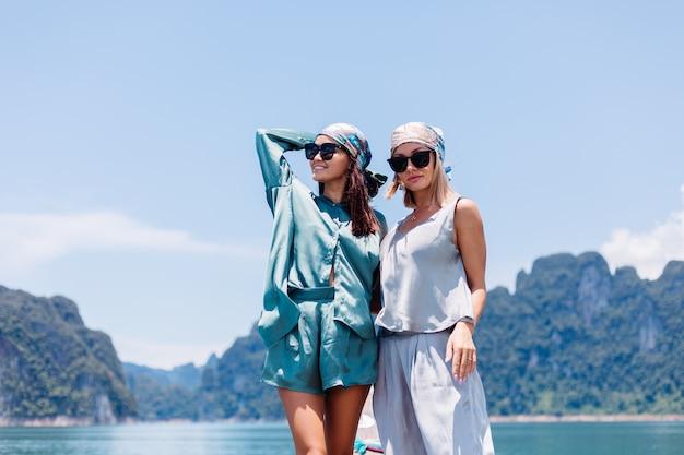 Due amici turisti blogger donna felice in vestito di seta e sciarpa e occhiali da sole in vacanza viaggiano intorno alla tailandia sulla barca asiatica, parco nazionale di khao sok.