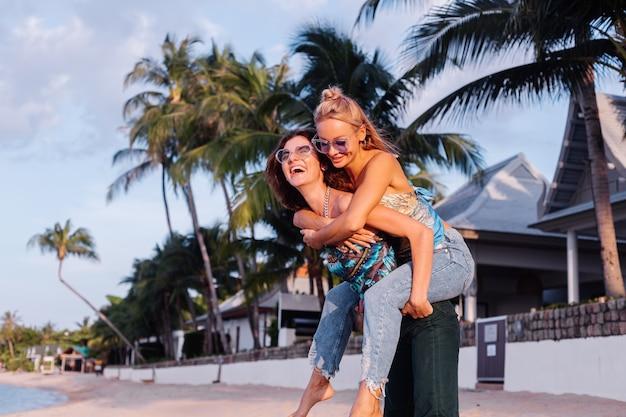 Due amici della donna felice con gli occhiali da sole in vacanza nel paese tropicale
