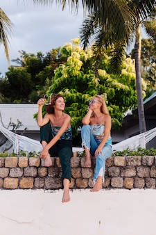 Two happy woman friends with sunglasses on vacation in tropical country