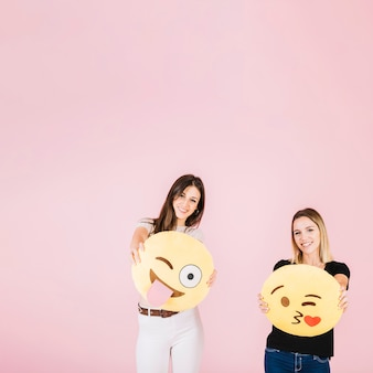 Two happy woman with different emoji icons on pink background