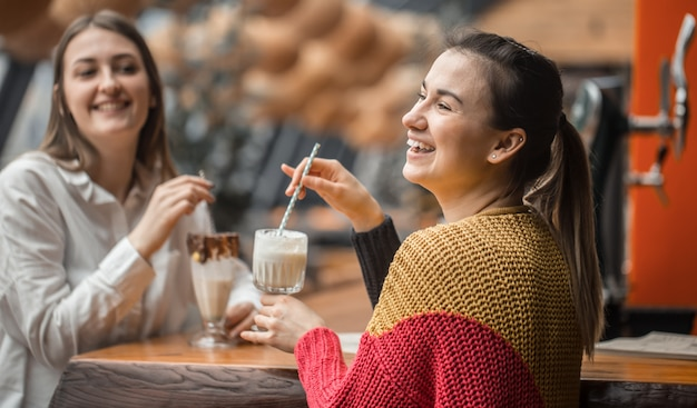 Two happy women are sitting in a cafe, drinking milkshakes,