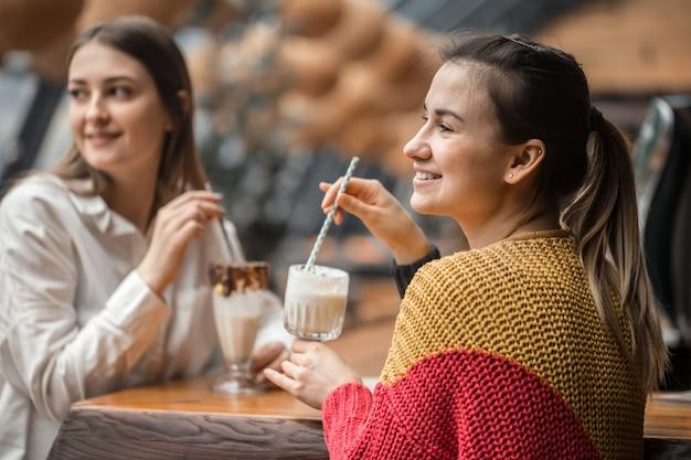 Две счастливые женщины сидят в кафе, пьют молочные коктейли,