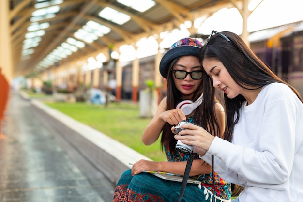 Two happy women are taking pictures while traveling at the train station. tourism concept