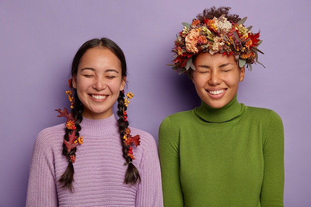 Two happy women being best friends, have fun laugh while make photo, decorate hair with autumn leaves, keep eyes shut, have broad smiles, enjoy good time, stand closely against purple background