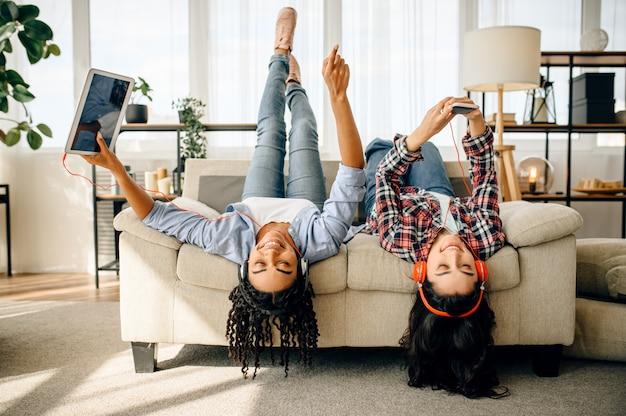 2人の幸せな女性は、家で逆さまに音楽を聴くことを楽しんでいます。イヤホンのかわいいガールフレンドは部屋でリラックスし、サウンド愛好家はソファで休んで、女性の友人は一緒にレジャー