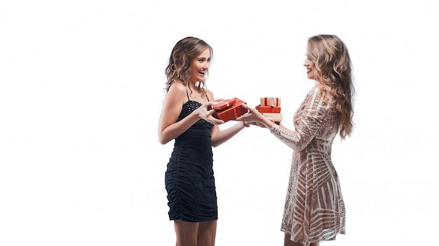 Two happy women friends exchanging presents isolated on white