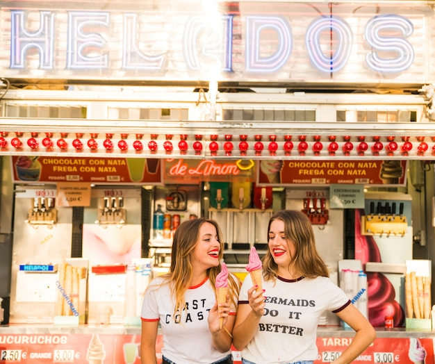 Two happy women holding ice cream at amusement park