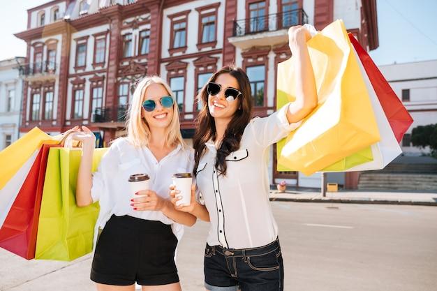 Две счастливые женщины держат хозяйственные сумки и веселятся, смеясь на улице