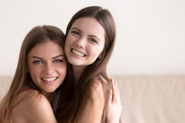 Two happy women hugging and looking in camera