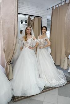 Две счастливые женщины в свадебных платьях позируют в салоне