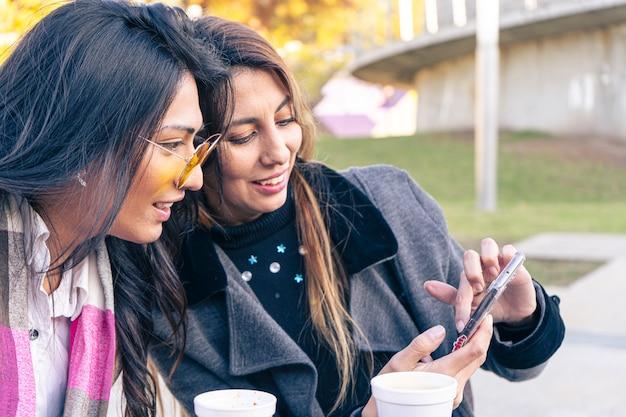 두 명의 행복한 라틴 여성 친구나 자매가 겨울에 기기를 보고 있는 커피숍 테라스에서 스마트 폰을 공유합니다.
