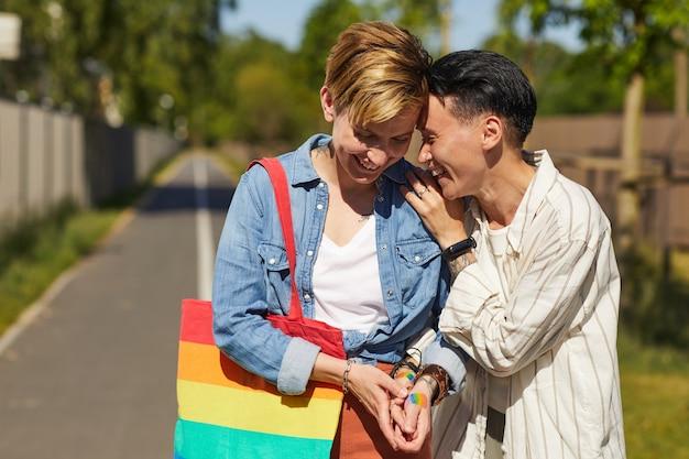 屋外を歩きながら笑って楽しんでいる2人の幸せな女性