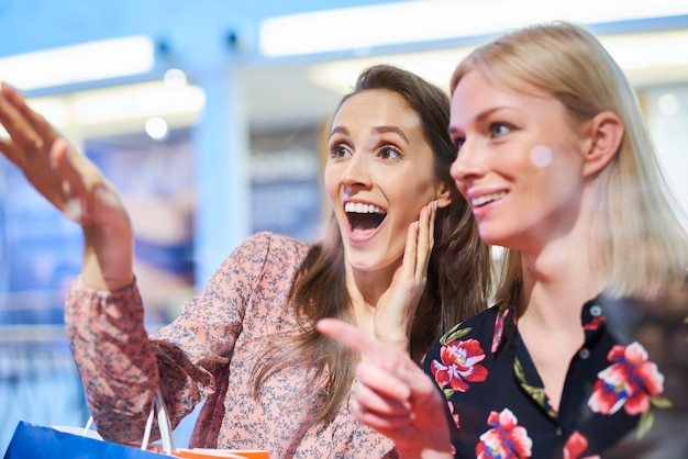 Two happy women looking at window display