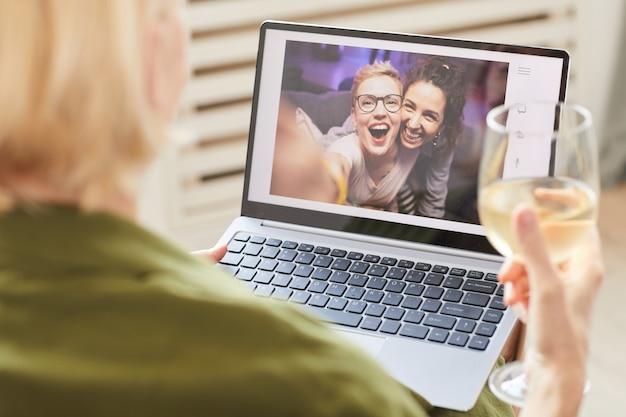 Две счастливые женщины на мониторе компьютера разговаривают онлайн со своим другом, который сидит дома