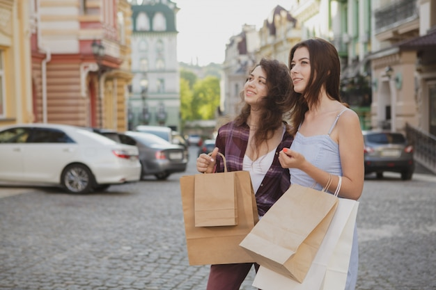 Two happy women sightseeing together after shopping on their vacation