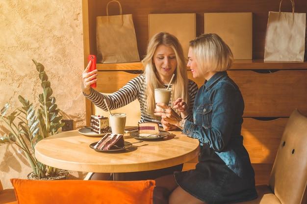 Две счастливые женщины сидят в кафе и делают селфи по телефону, пьют коктейль, рассказывают друг другу забавные истории, находясь в хорошем настроении, счастливо смеясь. лучшие друзья