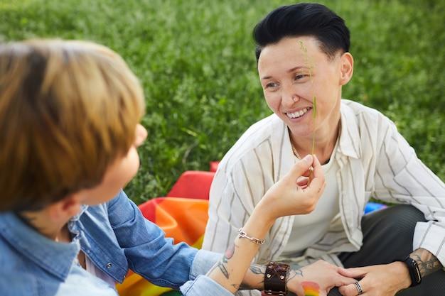 緑の芝生に座って、公園でピクニックをしている笑顔の2人の幸せな女性