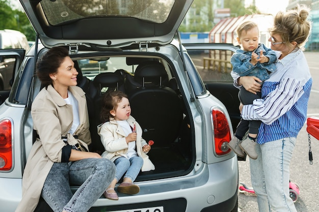 Two happy women and their beautiful kids beside a car on a parking lot