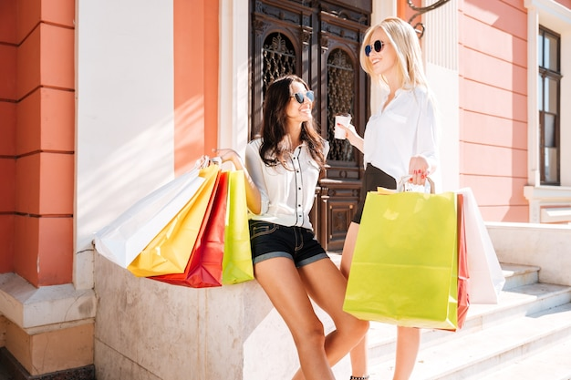 Two happy women with shopping bags sitting on steps